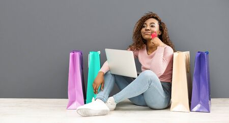 Dreamy mixed race girl with credit card making shopping using laptop, sitting on floor among shopping bags, panorama with copy space, grey background
