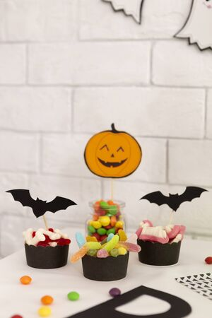 Trick or treat. Different scary Halloween candies with paper bats and pumpkin over bricks wall background, vertical panorama