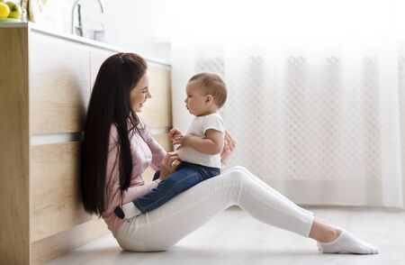Cute conversation. Young mother embracing with her baby, sitting on kitchen floor, empty space