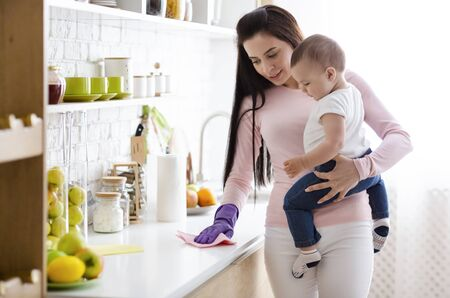 Domestic chores at maternity leave. Young mother with baby boy cleaning kitchen at home, free space Stock Photo