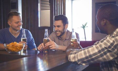 Three cheerful multiracial guys spending time together in pub, talking and drinking beer, panorama with copy space Фото со стока