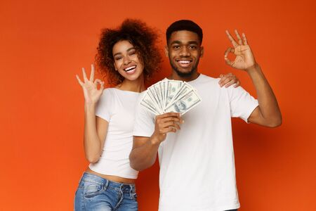 Great investment. Happy african man and woman gesturing OK sign with lots of money, orange studio background Stock Photo