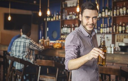 Handsome young guy raising beer bottle and smiling, spending time with friends at pub, panorama with copy space