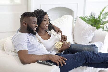 Relaxed black couple watching tv, sitting on couch with popcorn at home, side view