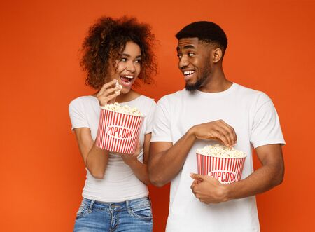 Enjoying cinema snack. Positive african man and woman eating popcorn, flirting with each other, orange studio background