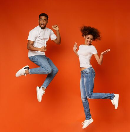 Carefree african american man and woman jumping in air, orange studio background