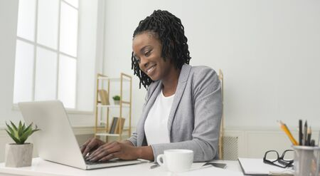 Smiling African American Businesswoman Using Laptop Working On New Project In Modern Office. Successful Entrepreneurship