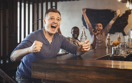 Excited football fan clenching fists and shouting, watching game in bar, drinking beer with his friends, panorama