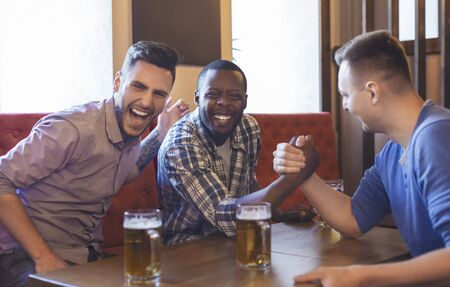 Arm Wrestling. Male Friends Having Fun And Drinking Beer In Bar