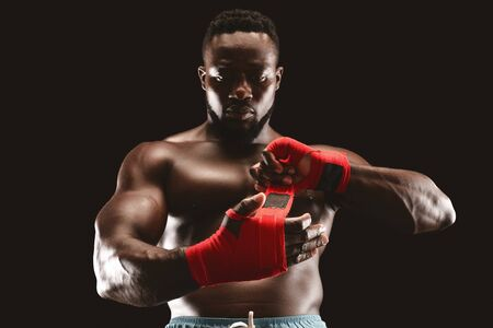 Focused young african man getting ready for fight, wrapping fists with red boxing bandage, black studio background Standard-Bild - 130628572