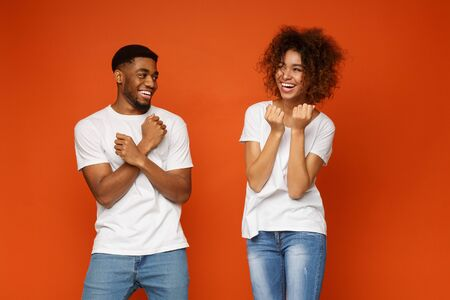 Cheerful african man and woman fooling, clenching fists on orange background
