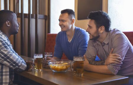 Cheerful mixed race mates talking while drinking beer at pub on friday night Фото со стока