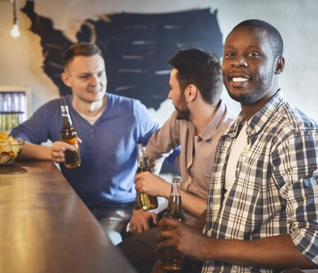 Mutliracial young friends watching football match at bar together, drinking beer and having conversation