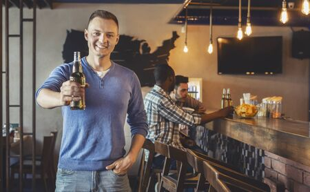 Cheerful young guy raising beer bottle and smiling, spending time with friends at bar, panorama with free space