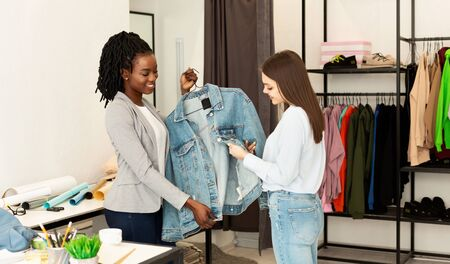 Showroom Shopping. Clothing Designer Showing Trendy Jacket To Her Client In Fashion Store. Copy Space
