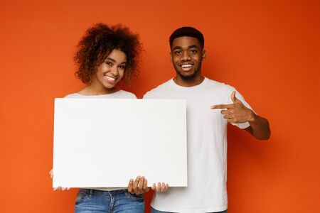 Awesome offer. Positive black man and woman pointing at white empty board and smiling, orange studio background