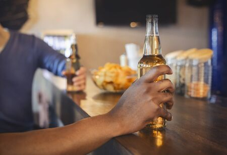 Cropped image of friends with beer bottles and chips sitting at pub, copy space Фото со стока