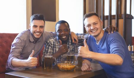 Cheerful mixed race friends taking photo with thumbs up at bar, drinking beer
