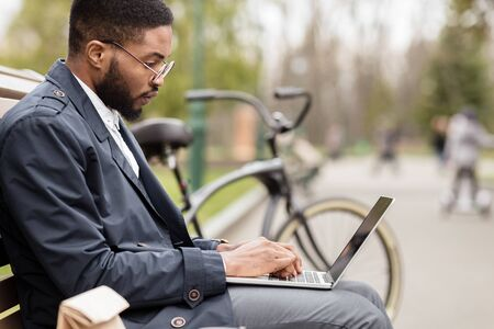 Afro businessman using laptop in park, sitting on bench with bike nearby, free space Imagens