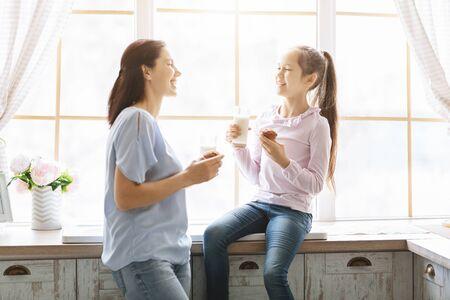 Mutter und Tochter essen Muffins und trinken Milch in der Nähe des Küchenfensters, haben zusammen Spaß