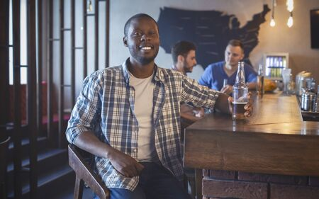 Smiling african guy drinking beer with friends, spending time together at bar, panorama with copy space