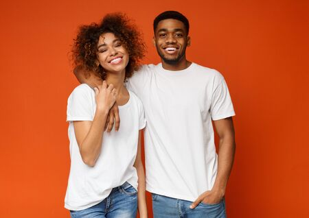 Positive lifestyle. Happy african millennials embracing on orange background