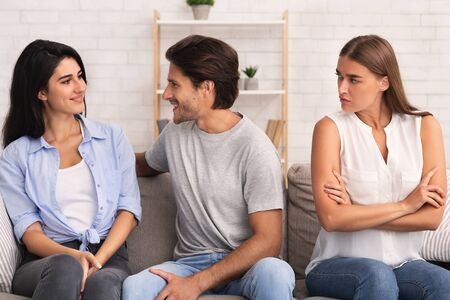 Jealousy. Angry Girlfriend Looking At Boyfriend Flirting With Another Girl Sitting On Sofa Indoor.
