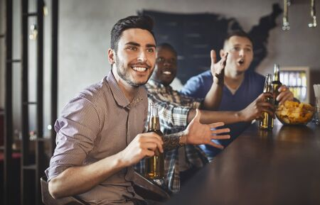 Mixed Race Football Fans Watching Match In Bar And Drinking Beer, celebrating victory, panorama with copy space