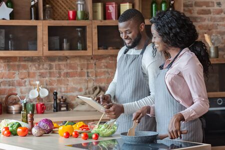Lovely african couple using digital tablet while cooking vegetarian meal, copy space