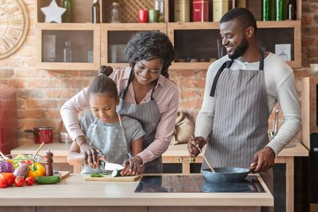 Cheerful African Woman Showing Her Lovely Daughter How To Cut Cucumber, happy father watching them, cooking together at kitchen, copy space
