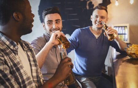 Multiracial friends talking while watching football game in bar, drinking beer, having fun together