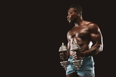Black muscular male fitness model doing workout with dumbbells, black studio background, empty space