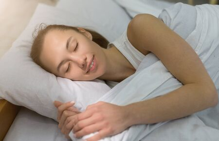 Beautiful young woman sleeping in bed comfortably. Sunbeam dawn on her face