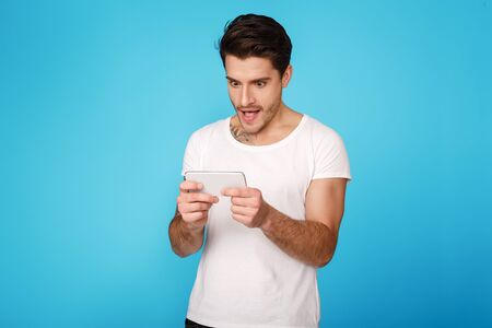 Concentrated young man playing on smartphone over blue studio background