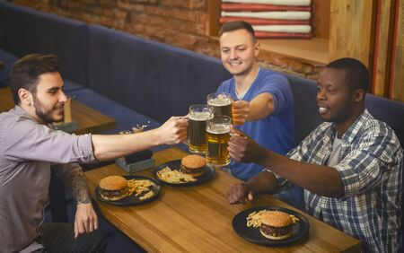 Top view of multiracial mates clinking mugs with beer in pub, empty space Фото со стока