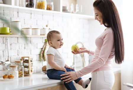 Healthy eating for baby. Caring mother offering fresh green apple to her infant at kitchen, free space Stock Photo