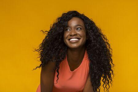 Aufgeregte afroamerikanische junge Frau, die beiseite schaut, lächelt, gelber Hintergrund Standard-Bild