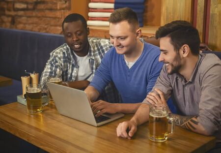 Dating website. Three happy young men drinking beer and using lapop in pub together