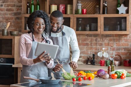 Modern technologies in everyday life. Black couple using digital tablet and cooking dinner in kitchen together, copy space