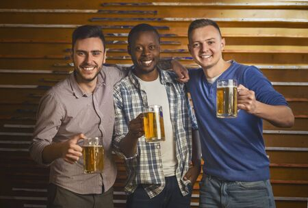 Happy young multiracial mates posing with glasses of beer at pub, bachelor party