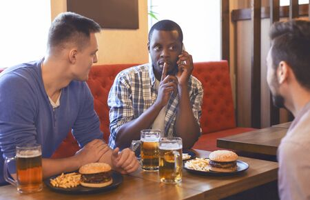 Shhh...girlfriend is calling. Young african guy talking to his girlfriend by phone while drinking beer with friends at bar, free space