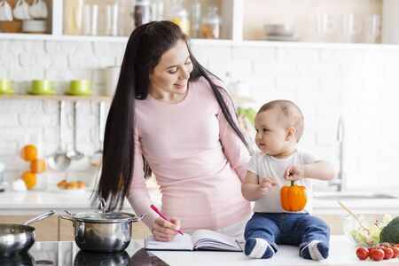 Happy domestic life. Mommy noting thoughts, sitting with baby at kitchen, free space Stock Photo