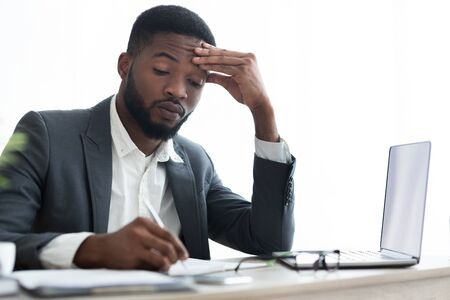 Focused african american employee taking notes in notebook at workplace in office, copy space