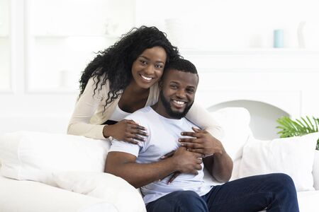 Portrait Of Smiling African American Couple Posing To Camera At Home, Copy Space