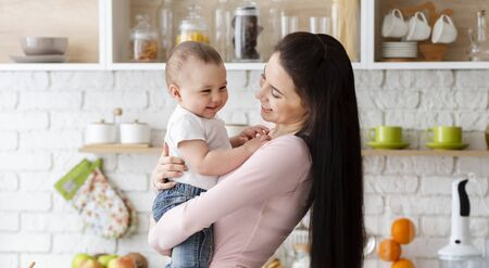 Kitchen laught. Mother playing with her cute smiling toddler, panorama Stock Photo