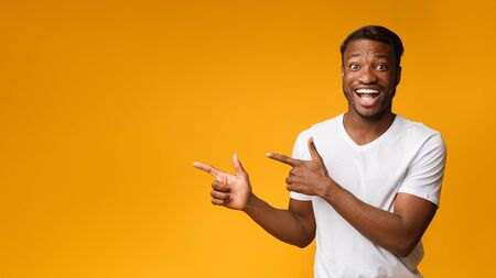 Look There. Excited African American Guy Pointing Fingers Aside At Copy Space On Yellow Studio Background. Panorama Фото со стока