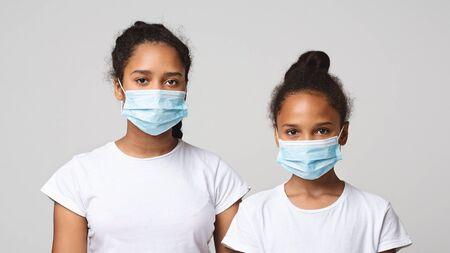 Virus- und Grippekonzept. Zwei junge afrikanische Schwestern, die medizinische Masken über grauem Studiohintergrund tragen, Panorama