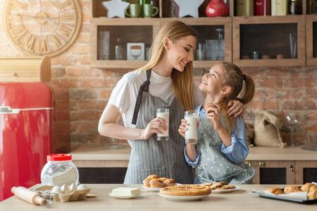 Pretty mom and daughter spending time together at kitchen, eating cupcakes and drinking milk, copy space