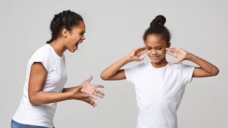 Generation conflict. Furious african girl quarreling at her sister, little girl closing her ears, grey studio background, panorama