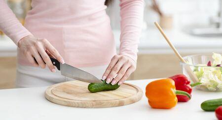 Cocinar en casa. Mujer cortando verduras frescas para ensalada sobre tabla de madera, panorama